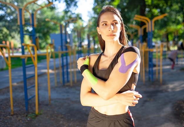 Portret van aantrekkelijke gespierde brunette vrouw, gekleed in zwarte sport-outfit