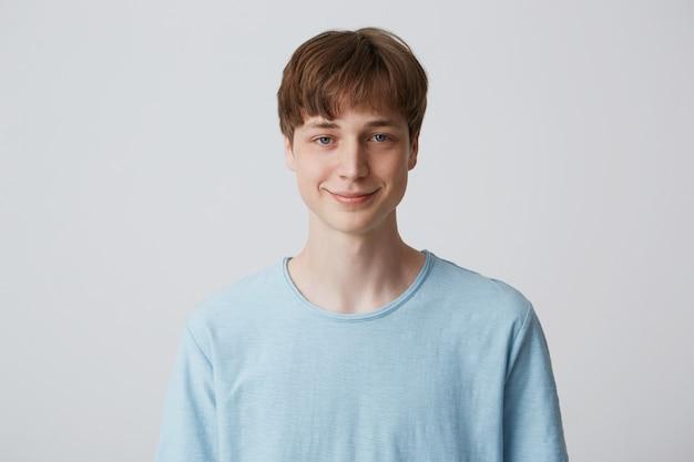 Portret van aantrekkelijke glimlachende blauwogige jonge kerel met kort kapsel draagt blauwe t-shirt staan