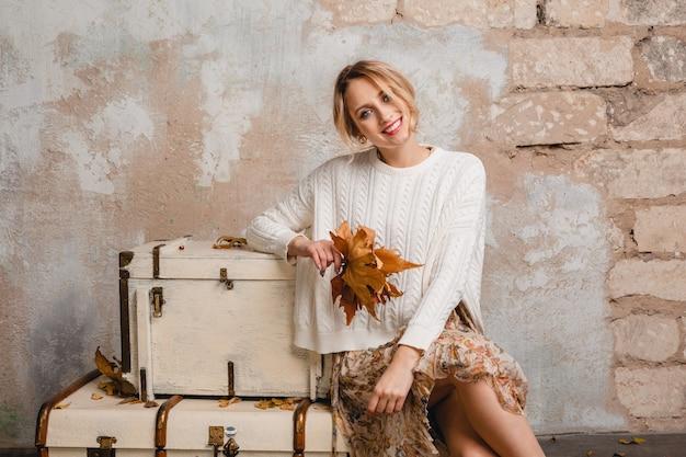 Portret van aantrekkelijke glimlachende stijlvolle blonde vrouw in witte gebreide trui zittend op koffers in straat tegen vintage muur