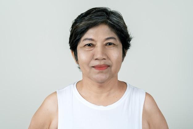 Portret van aantrekkelijke hogere aziatische oude vrouw die en camera in studio glimlacht bekijkt