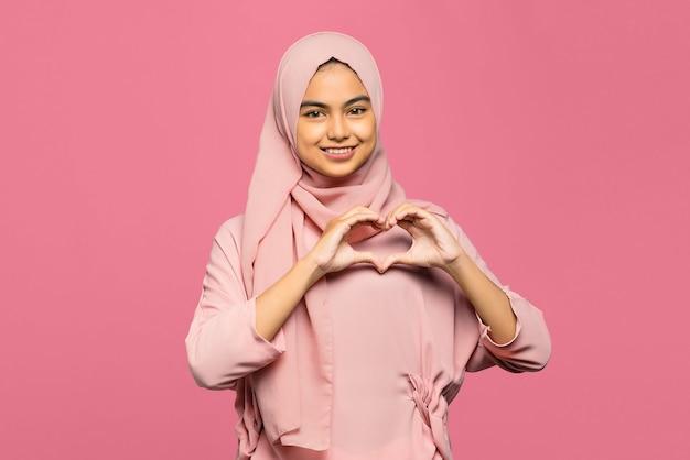 Portret van aantrekkelijke jonge aziatische vrouw maakt hartvorm gebaar met lachend gezicht