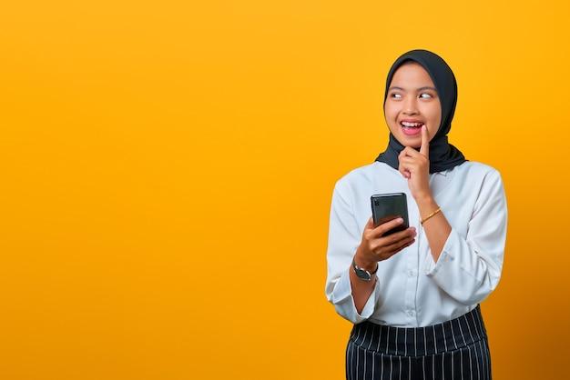 Portret van aantrekkelijke jonge aziatische vrouw met mobiele telefoon en hand op lippen op gele achtergrond