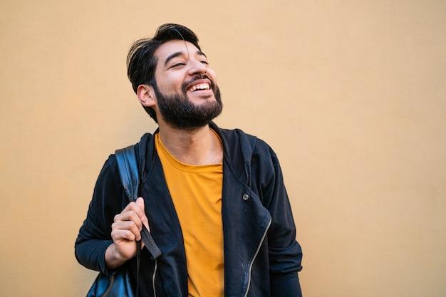 Portret van aantrekkelijke jonge bebaarde man met rugzak op zijn schouders tegen gele ruimte. stedelijk concept.