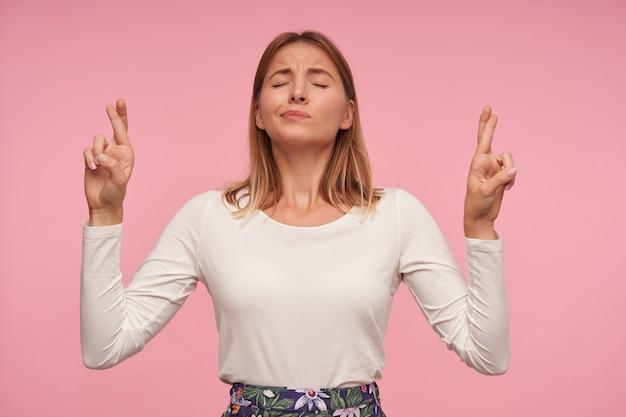 Portret van aantrekkelijke jonge blonde vrouw met casual kapsel handen opheffen met gekruiste vingers, in de hoop dat haar dromen zullen uitkomen en ogen gesloten houden, geïsoleerd op roze achtergrond