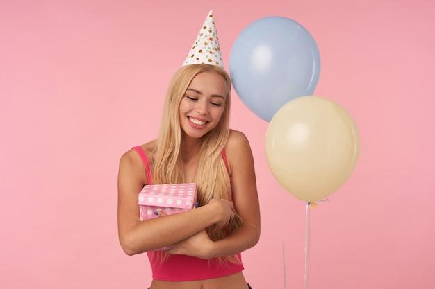 Portret van aantrekkelijke jonge blonde vrouw met lang haar geschenkdoos houden en oprecht glimlachend met gesloten ogen, haar aangename emoties tonen op roze achtergrond