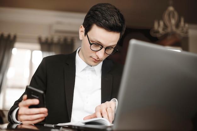 Portret van aantrekkelijke jonge ceo zit in zijn kantoor en werkt op zijn laptop terwijl hij een smartphone vasthoudt.