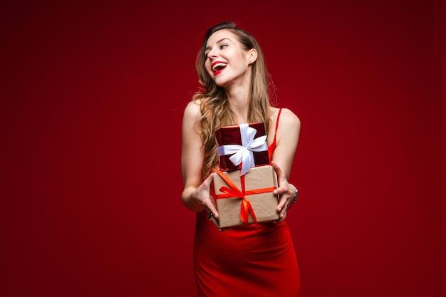 Portret van aantrekkelijke jonge dame in rode zijden jurk met twee kleine verpakte cadeautjes in de armen en weg glimlachen