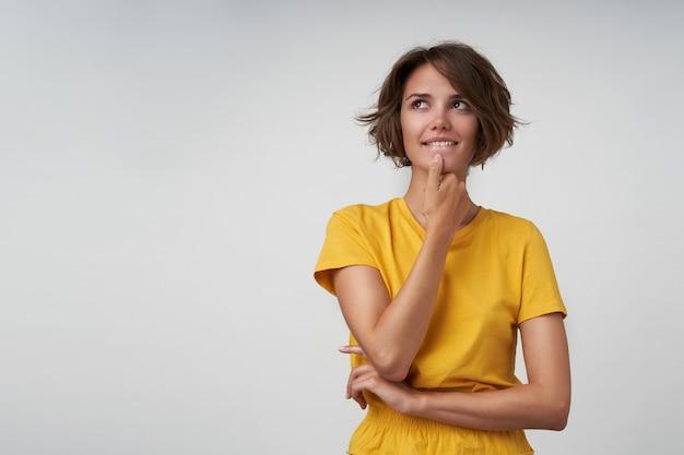 Portret van aantrekkelijke jonge dame met kort bruin haar die peinzend opzij kijkt en haar kin met de hand vasthoudt, gele vrijetijdskleding draagt terwijl hij staat