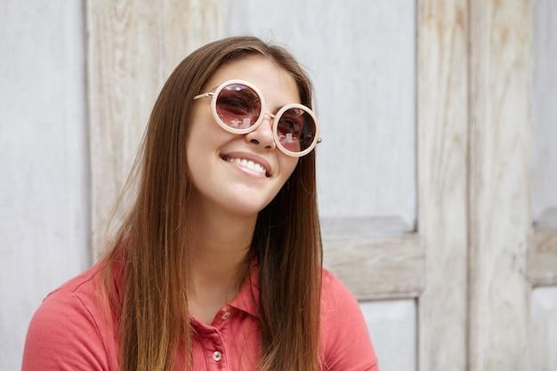 Portret van aantrekkelijke jonge dame met lang blond haar dagdromen, gelukkig glimlachen, vreugdevolle en geïnspireerde blik hebben.