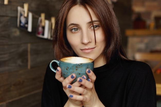 Portret van aantrekkelijke jonge enige brunette vrouw met doordachte dromerige blik