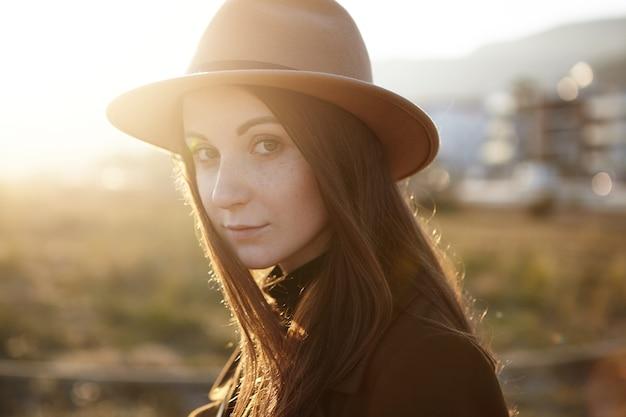 Portret van aantrekkelijke jonge europese vrouw, gekleed in trendy hoed en jas close-up