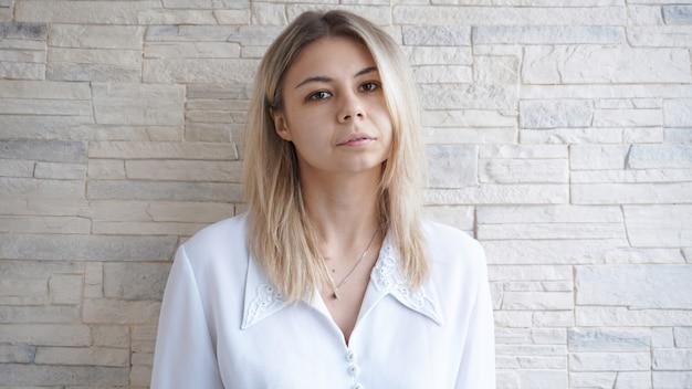 Portret van aantrekkelijke jonge europese zakenvrouw op bakstenen muur. leiderschap en leidersconcept