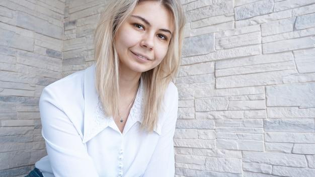 Portret van aantrekkelijke jonge europese zakenvrouw op bakstenen muur. succes concept