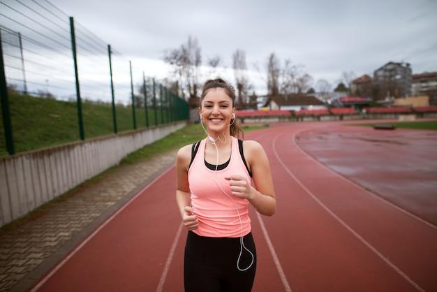 Portret van aantrekkelijke jonge gelukkig fitness meisje joggen terwijl u luistert naar muziek buiten in de buurt van het voetbalveld.