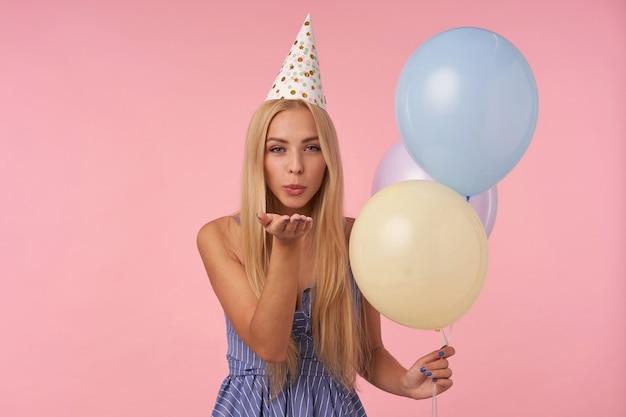 Portret van aantrekkelijke jonge langharige vrouw viert verjaardag met veelkleurige lucht ballonnen, camera positief kijken en blazen lucht kus met samengeknepen lippen