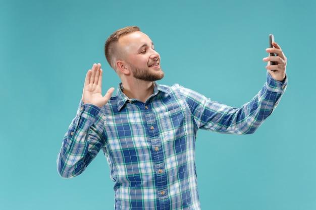 Portret van aantrekkelijke jonge man die een selfie met zijn smartphone