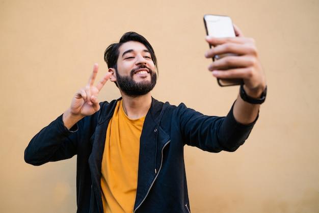 Portret van aantrekkelijke jonge man die selfies met zijn mophile telefoon neemt tegen gele muur.