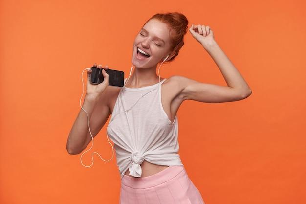 Portret van aantrekkelijke jonge readhead vrouw met foxy haar in knoop luisteren naar muziek met koptelefoon, dragen witte top en roze rok, dansen op oranje achtergrond met gesloten ogen