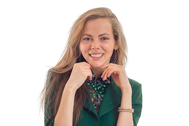 Portret van aantrekkelijke jonge vrouw die in de camera kijkt, houdt uw handen dichtbij uw gezicht en glimlacht geïsoleerd op witte muur
