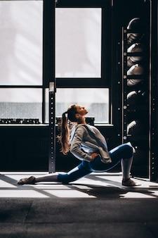Portret van aantrekkelijke jonge vrouw die yoga of pilates oefening doet