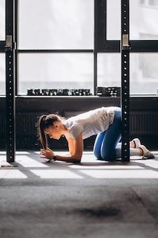 Portret van aantrekkelijke jonge vrouw die yoga of pilatesoefening doet