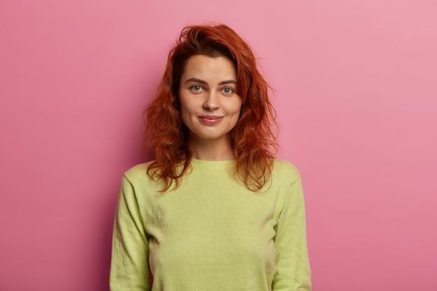 Portret van aantrekkelijke jonge vrouw heeft natuurlijk rood haar, kijkt direct naar de camera met een zachte glimlach