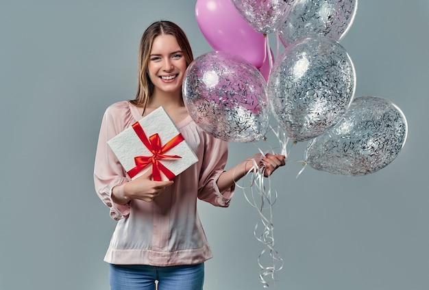Portret van aantrekkelijke jonge vrouw in blouse staat op grijs met geschenkdoos in handen en ballonnen.