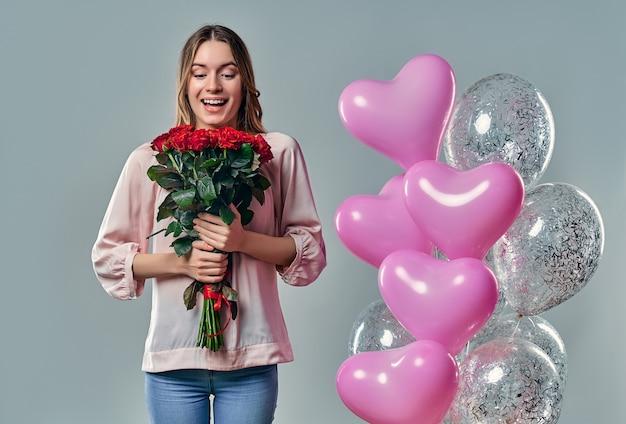Portret van aantrekkelijke jonge vrouw in blouse staat op grijs met rode rozen in handen en ballonnen.