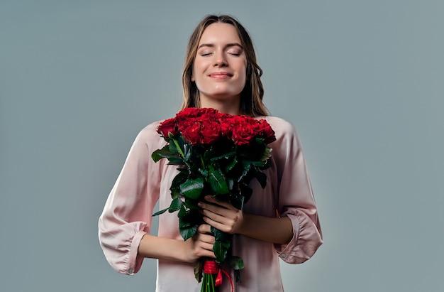 Portret van aantrekkelijke jonge vrouw in blouse staat op grijs met rode rozen in handen en geniet van de geur van bloemen.