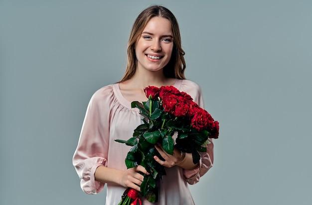 Portret van aantrekkelijke jonge vrouw in blouse staat op grijs met rode rozen in handen en glimlachen.