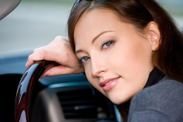 Portret van aantrekkelijke jonge vrouw in de nieuwe auto - buitenshuis