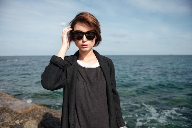 Portret van aantrekkelijke jonge vrouw in zonnebril die zich aan kust bevindt