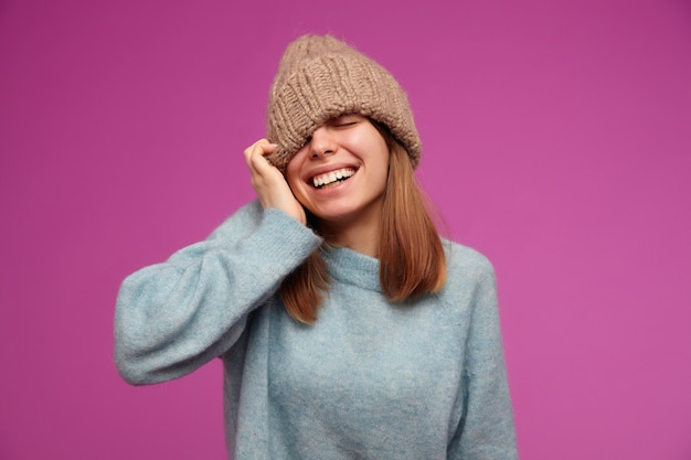 Portret van aantrekkelijke, jonge vrouw met donkerbruin lang haar. het dragen van blauwe trui en gebreide muts. trekt hoed over oog en lachend op geïsoleerde over paarse muur