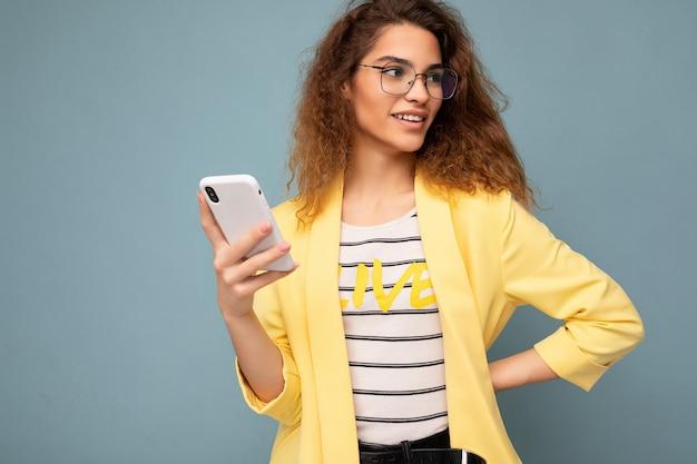 Portret van aantrekkelijke jonge vrouw met krullend donker blond haar, gekleed in een gele jas en optische bril, geïsoleerd op de achtergrond, vasthoudend en gebruikend telefoon kijkend naar de kant