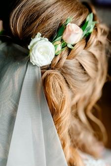 Portret van aantrekkelijke jonge vrouw met mooi kapsel en stijlvolle haartoebehoren, achteraanzicht