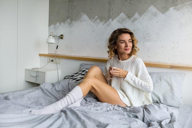 Portret van aantrekkelijke jonge vrouw zittend op bed in de ochtend, koffie drinken in de beker