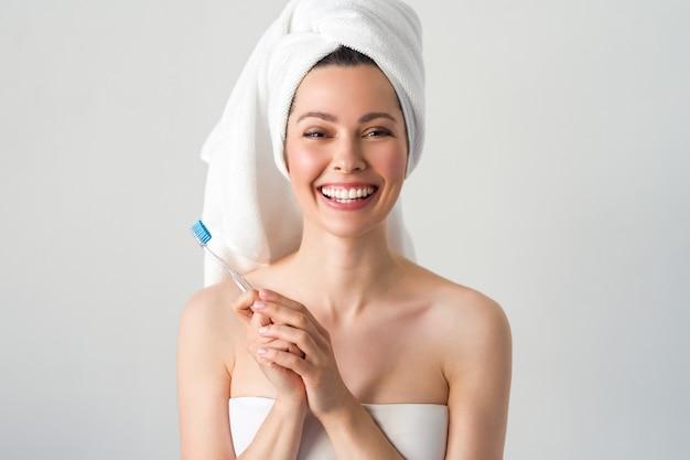 Portret van aantrekkelijke kaukasische glimlachende vrouw die op wit muurschot wordt geïsoleerd dat haar tanden borstelt.