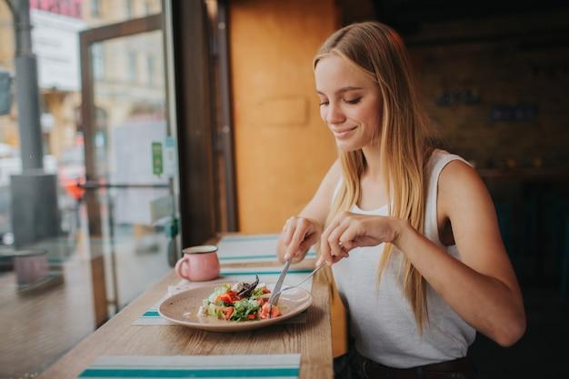 Portret van aantrekkelijke kaukasische glimlachende vrouw die salade eet