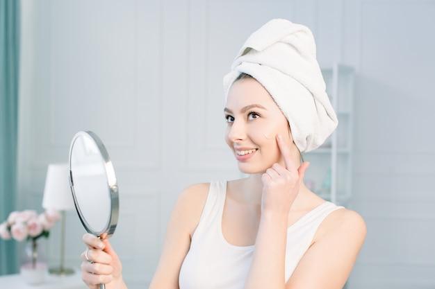 Portret van aantrekkelijke kaukasische glimlachende vrouw op wit studioschot dat haar gezicht schoonmaakt bekijkend de spiegel die stichting op gezichtshuid toepast