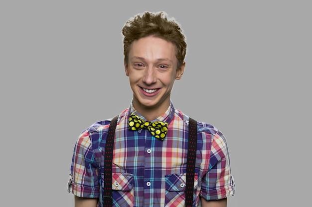 Portret van aantrekkelijke kaukasische tiener. gelukkig adolescente man camera kijken op grijze achtergrond.