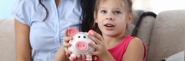 Portret van aantrekkelijke klein kind met roze spaarvarken.
