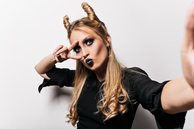 Portret van aantrekkelijke kleine heks selfie maken. nieuwsgierige jonge vrouw met halloween-make-up binnen stellen.