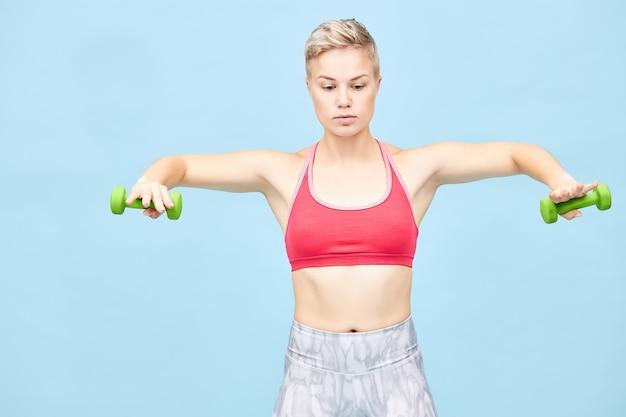 Portret van aantrekkelijke kortharige blonde meisje met atletisch lichaam trainen, gelaatsuitdrukking hebben, armen op schouderhoogte houden met halters in haar handen, armspieren versterken