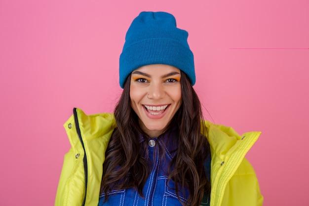 Portret van aantrekkelijke lachende stijlvolle vrouw poseren in winter fashion look op roze muur in felle neon gele jas, blauwe gebreide muts dragen, gekleed in warme kleding