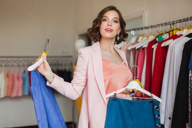 Portret van aantrekkelijke lachende vrouw met denim rok op hanger in kledingwinkel