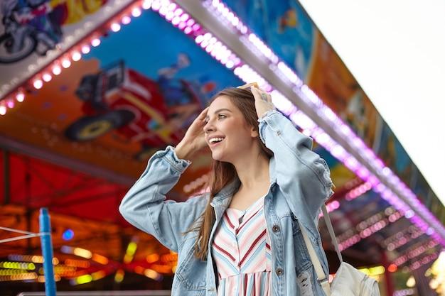 Portret van aantrekkelijke langharige jonge vrouw in jeans jas poseren over park van attracties, zonnebril op haar hoofd houden en vrolijk vooruit kijken Gratis Foto