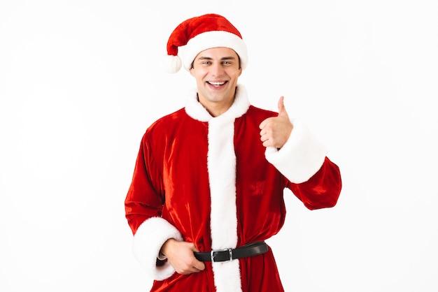 Portret van aantrekkelijke man 30s in kerstman kostuum en rode hoed glimlachen