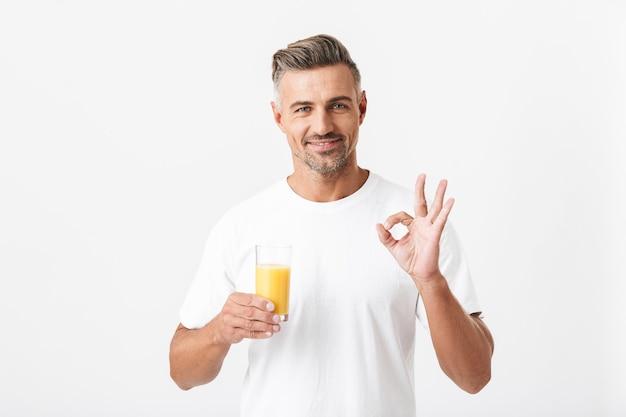 Portret van aantrekkelijke man 30s met borstelharen dragen casual t-shirt met ok teken terwijl glas sinaasappelsap geïsoleerd op wit
