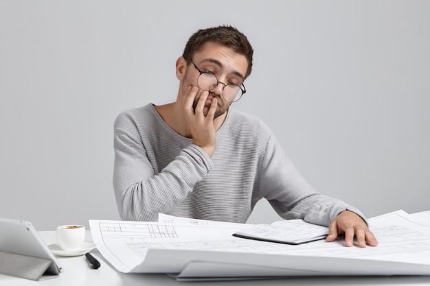 Portret van aantrekkelijke man draagt een ronde bril, kijkt verbaasd over blauwdrukken, heeft geen idee hoe hij schetsen moet tekenen