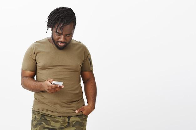 Portret van aantrekkelijke man in een bruin t-shirt poseren tegen de witte muur met zijn telefoon